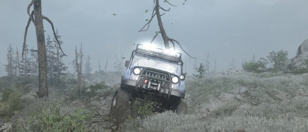 A jeep bouncing across rough terrain covered in vegetation.