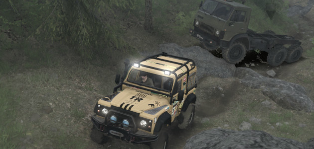 A truck and a land rover driving on a rough and bumpy road together.